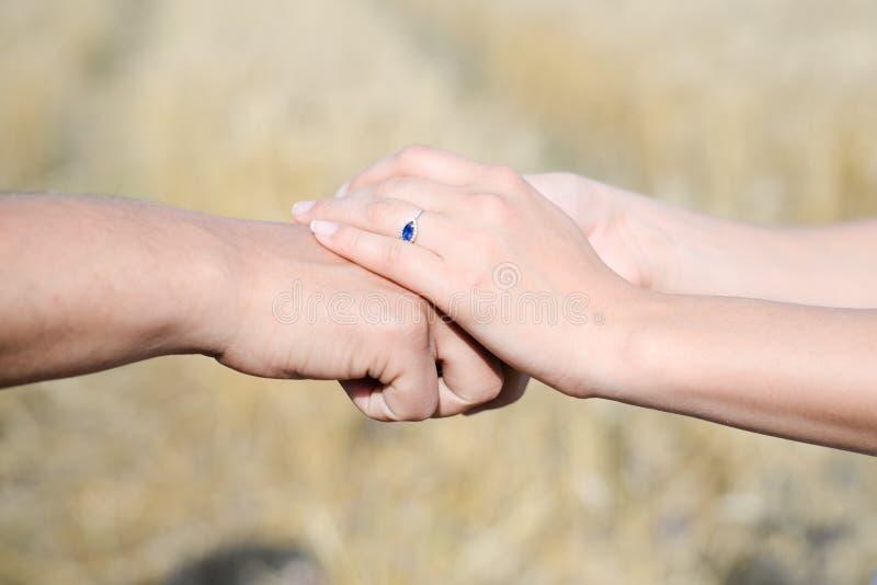 Kobiet ręki stawiać nad samiec ręką zdjęcia stock