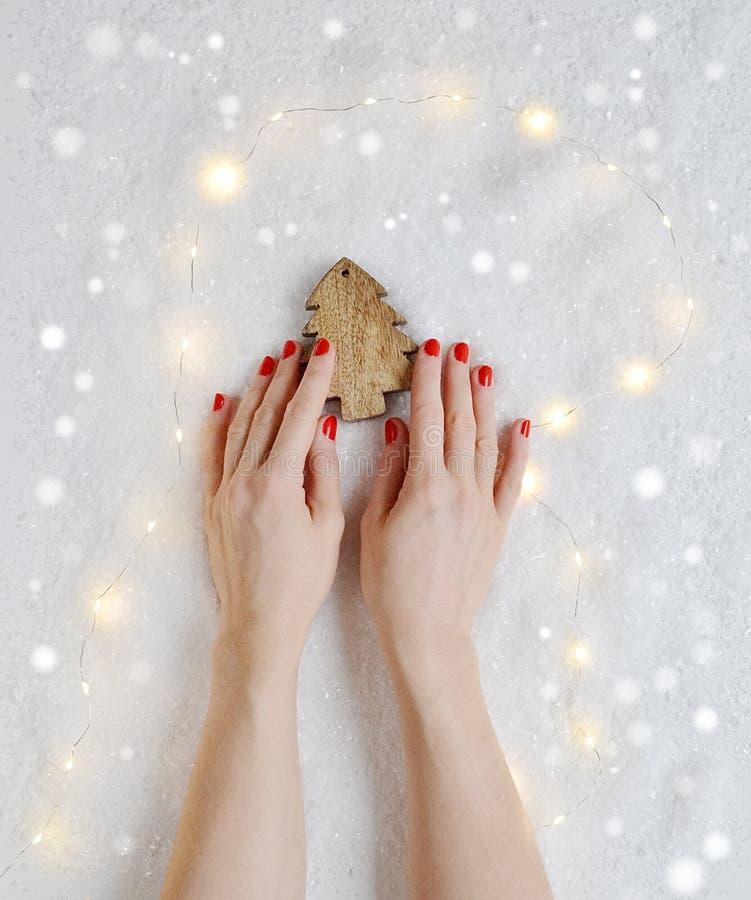 Kobiet ręki Trzyma boże narodzenie Zabawkarskiego wystroju Drewnianej sosny fotografia stock
