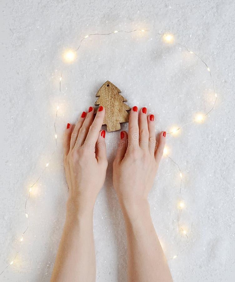Kobiet ręki Trzyma boże narodzenie Zabawkarskiego wystroju Drewnianej sosny fotografia royalty free