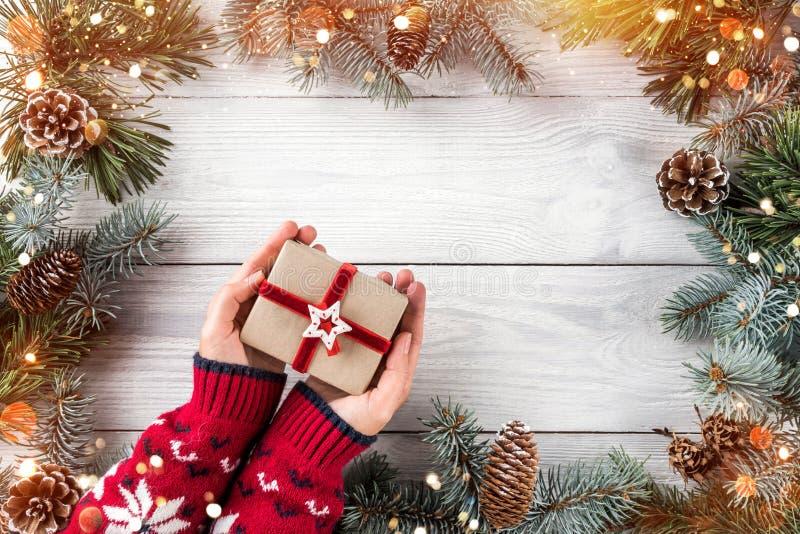 Kobiet ręki trzyma Bożenarodzeniowego prezenta pudełko na białym drewnianym tle z jodłą rozgałęziają się, sosna rożki Xmas i Szcz obraz stock