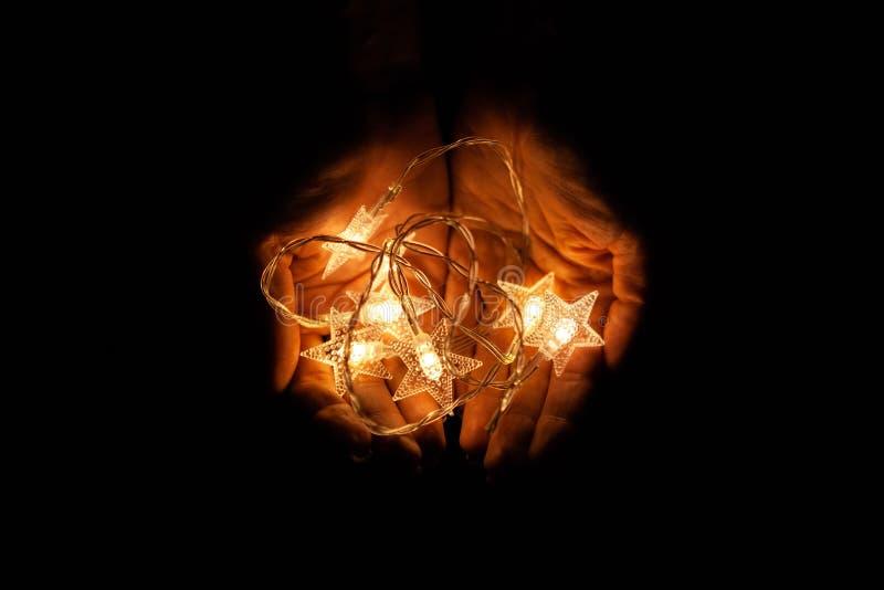 Kobiet ręki trzyma girlandę Dziewczyna z bożonarodzeniowymi światłami w jej rękach, ciepły Bożenarodzeniowy nastrój, miękka ostro zdjęcie royalty free