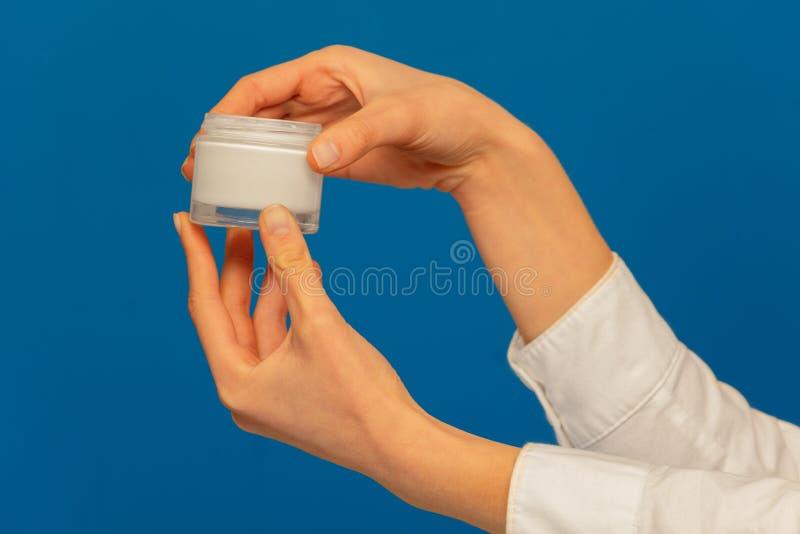 Kobiet ręki trzyma kosmetycznego kremowego zbiornika na błękicie zdjęcie royalty free