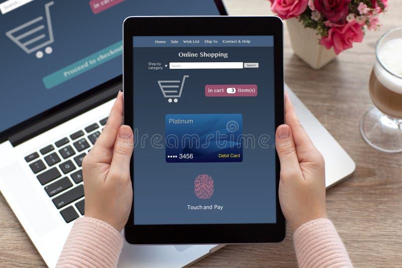 Kobiet ręki trzyma pastylka online zakupy dotykają noteboo i płacą zdjęcia stock