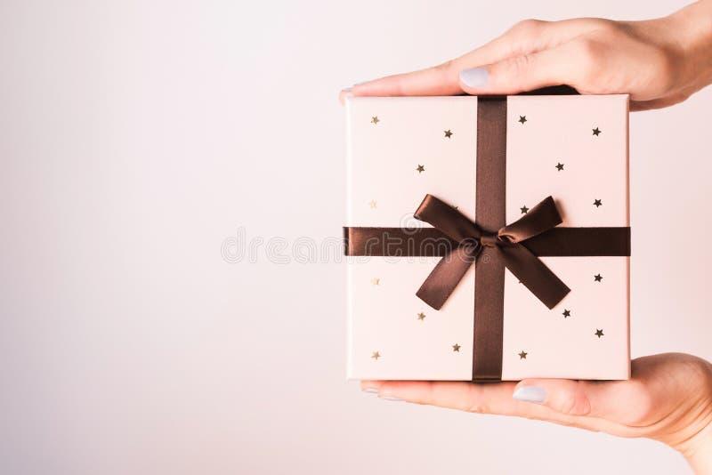 Kobiet ręki trzyma prezent z łękiem obraz stock
