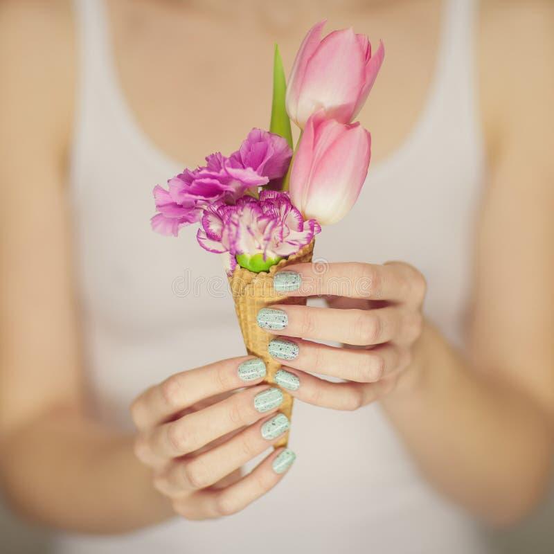 Kobiet ręki trzyma wiosna kwiaty w lody rożku, zmysłowy studio strzał zdjęcia stock