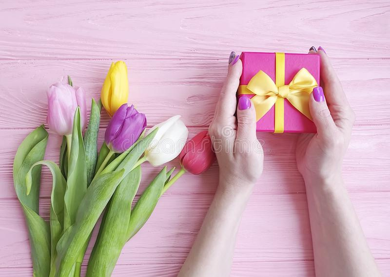 Kobiet ręki trzymają prezenta pudełka wakacje, bukiet tulipany na różowym drewnianym tle zdjęcie royalty free