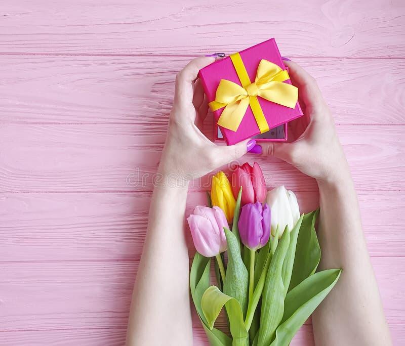 Kobiet ręki trzymają prezenta pudełka wakacje, przedstawiają bukiet tulipany na różowym drewnianym tle zdjęcie royalty free