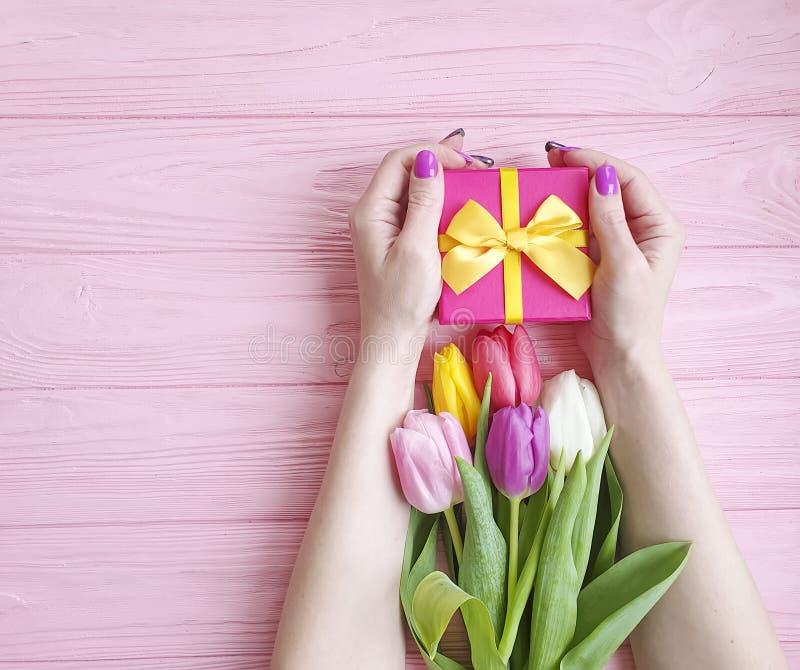 Kobiet ręki trzymają prezenta pudełka wakacyjnego urodziny, przedstawiają bukiet tulipany na różowym drewnianym tle zdjęcia stock
