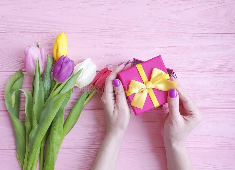 kobiet ręki trzymają prezenta pudełko, bukiet tulipany na różowym drewnianym tle obrazy stock