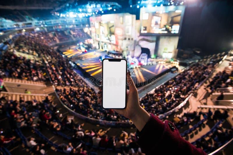 Kobiet ręki używać cyfrowego zastosowanie na mobilnym mądrze telefonie przy esport wydarzeniem przy dużą areną kosmos kopii zdjęcie royalty free