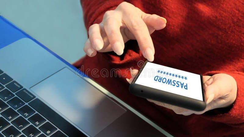 Kobiet r?ki w czerwieni ubraniach trzyma telefon kom?rkowego nad laptop klawiatura Parawanowy podpis: HAS?O Osobista dane ochrona fotografia stock