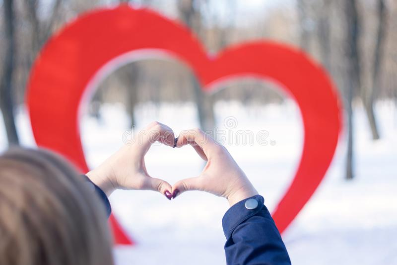 Kobiet ręki w formie serca przeciw tłu duża czerwona kierowa uliczna instalacja w zima parku Miłość, romans, obrazy stock