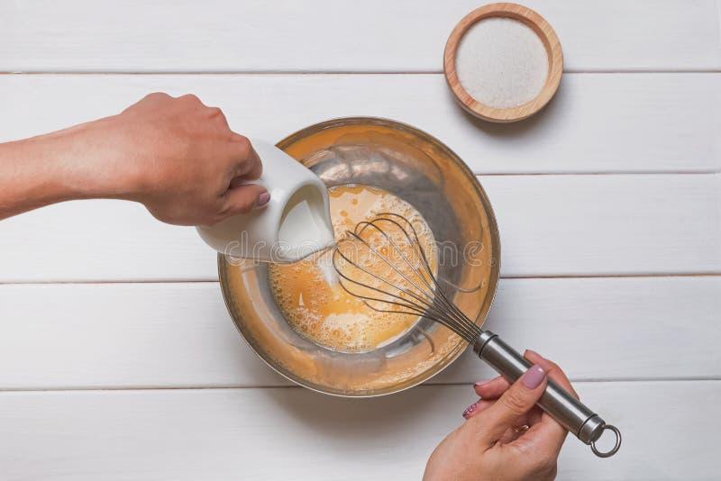 Kobiet ręki w górę mieszać i nalewać mleko jajka i cukier z wisk w wielkim pucharze zdjęcia stock