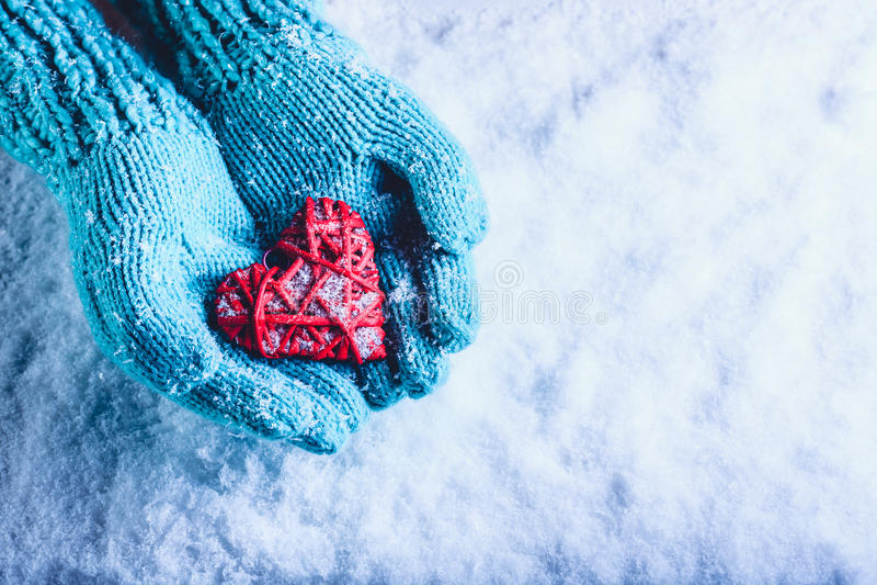 Kobiet ręki w lekka cyraneczka dziać mitynkach trzymają pięknego oplecionego rocznika czerwonego serce w śniegu St walentynki poj obrazy royalty free