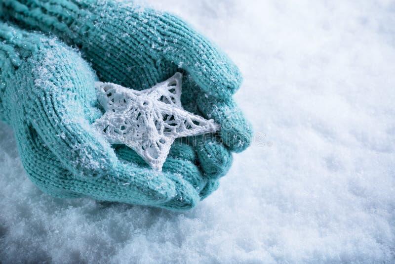 Kobiet ręki w lekkiej cyraneczce dziali mitynki z oplecioną biel gwiazdą na białym śnieżnym tle Zima i bożego narodzenia pojęcie obraz stock
