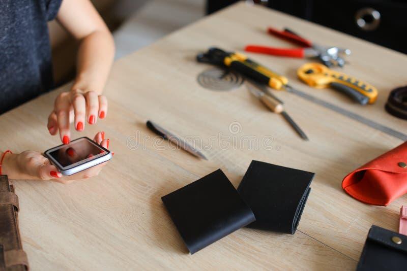 Kobiet ręki z czerwień gwoździami przy rzemiennym atelier używać smartphone, handmade portfle i narzędzia na stole, obraz stock