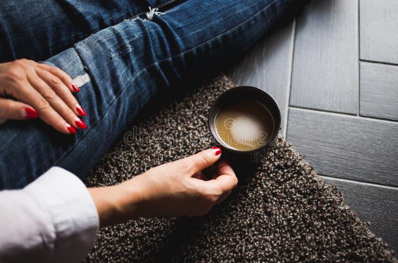 Kobiet ręki z czerwienią przybijają trzymać filiżanka kawy na kolanach podczas gdy siedzący na mące zdjęcia royalty free