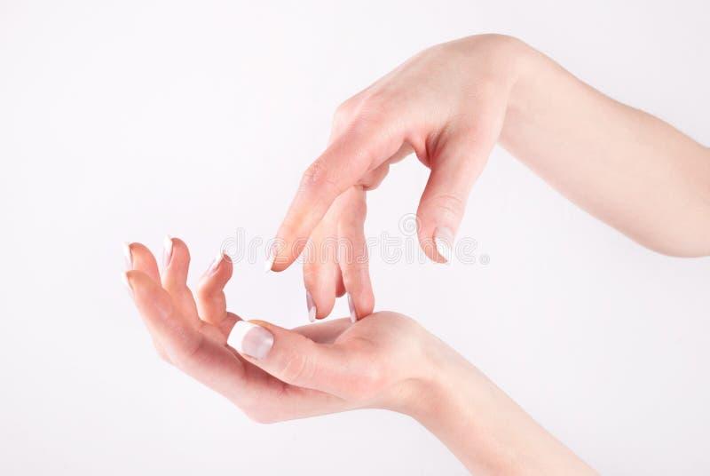Kobiet ręki z fachowym francuskim gwoździa manicure'em odizolowywającym na bielu obraz royalty free