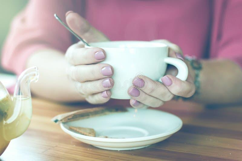 Kobiet ręki z filiżanką gorąca herbata dla zimna i temperatury Aro fotografia stock