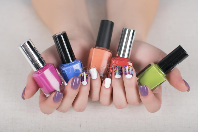 Kobiet ręki z gwoździ połysk i jaskrawym kolorowym manicure'em obraz stock