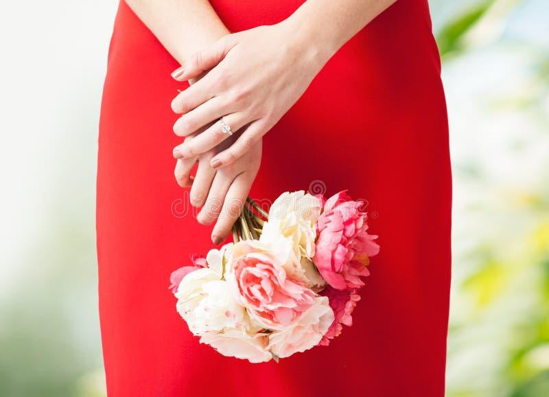 Kobiet ręki z kwiatami i pierścionkiem obrazy stock