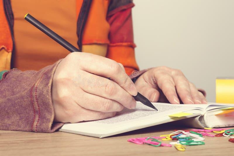 Kobiet ręki z pióra writing na książce fotografia stock