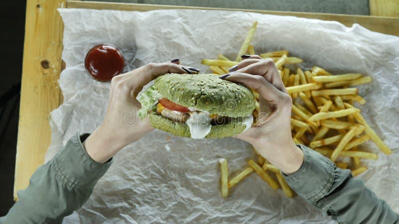 Kobiet ręki z pięknym manicure'em trzymają dużego soczystego hamburger z mięsnym plikiem i zieloną babeczką zdjęcie stock