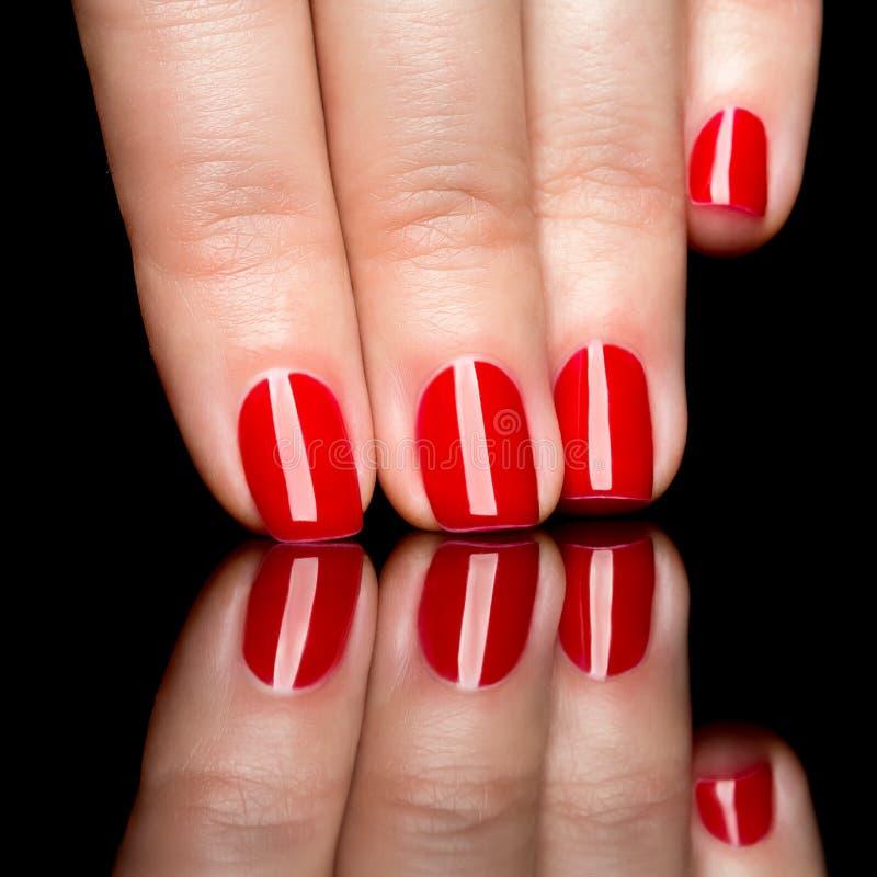 Kobiet ręki z robiącą manikiur czerwienią przybijają zbliżenie. obrazy royalty free