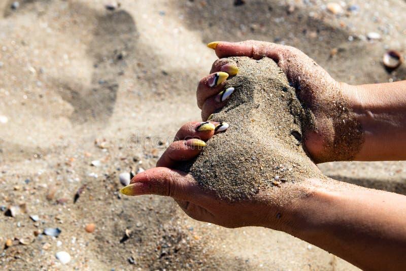 Kobiet ręki z robiącymi manikiur gwoździami trzymają gorącego piasek na plaży obrazy royalty free