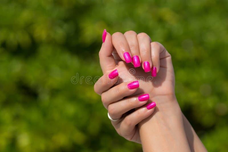 Kobiet ręki z robić manikiur menchiami przybijają zbliżenie Skóry i gwoździa samochód fotografia stock