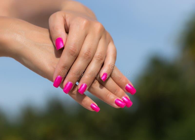 Kobiet ręki z robić manikiur menchiami przybijają zbliżenie Skóry i gwoździa samochód zdjęcie royalty free