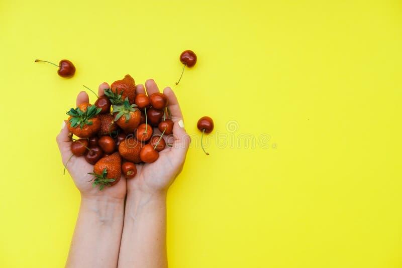 Kobiet ręki z truskawkami i wiśniami na żółtym backgrou zdjęcia stock