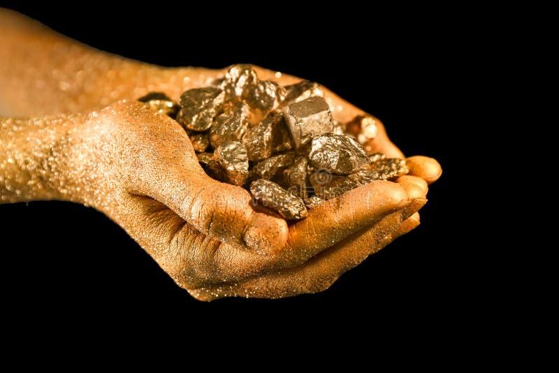 Kobiet ręki z złocistymi bryłkami na czarnym tle obrazy royalty free