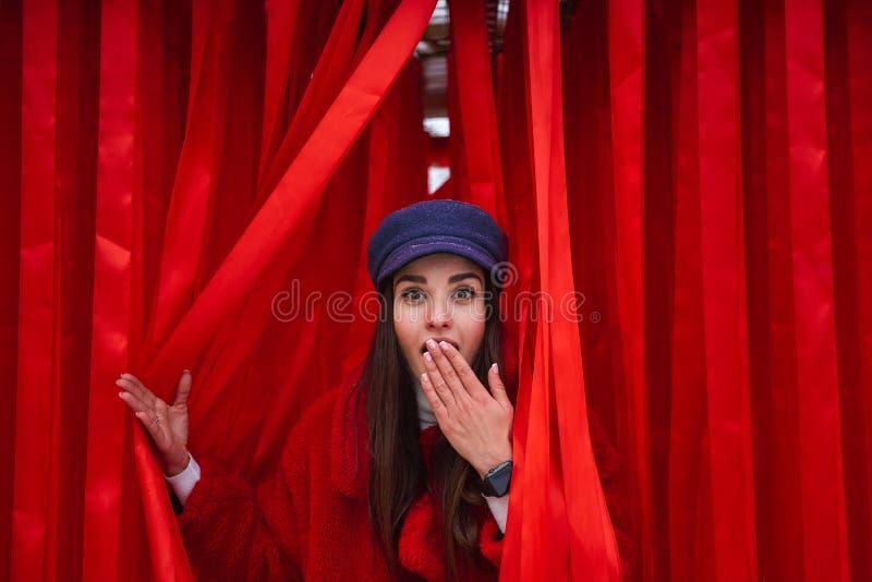 Kobiet spojrzenia między za czerwonej zasłonie zdjęcie stock