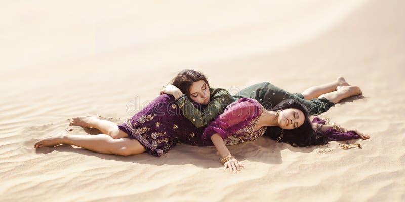 Kobiet spragniony kłaść w pustyni Gubjący w pustynnym durind sandshtorm zdjęcie stock