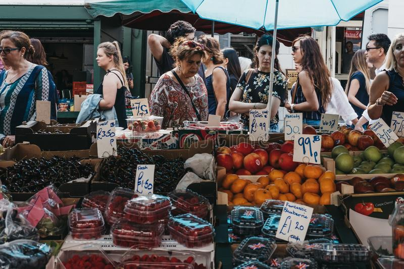 Kobiet stać bezczynnie wprowadzać na rynek kram z świeżymi owoc w Portobel zdjęcia stock