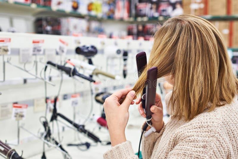 Kobiet wybiórek elektryczny prostować odprasowywa włosy w sklepie obraz stock
