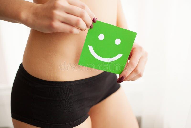 Kobiet zdrowie Zbliżenie Zdrowa kobieta Z Pięknym napadu schudnięcia ciałem Trzyma zieloną kartę Z Szczęśliwym W Czarnych majtasa zdjęcia royalty free