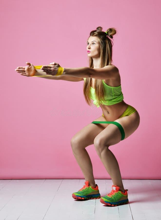 Kobieta ćwiczy robić postnatal treningowi Żeński sprawność fizyczna instruktor opracowywa z gumowym oporu zespołem na nowożytnych zdjęcia royalty free