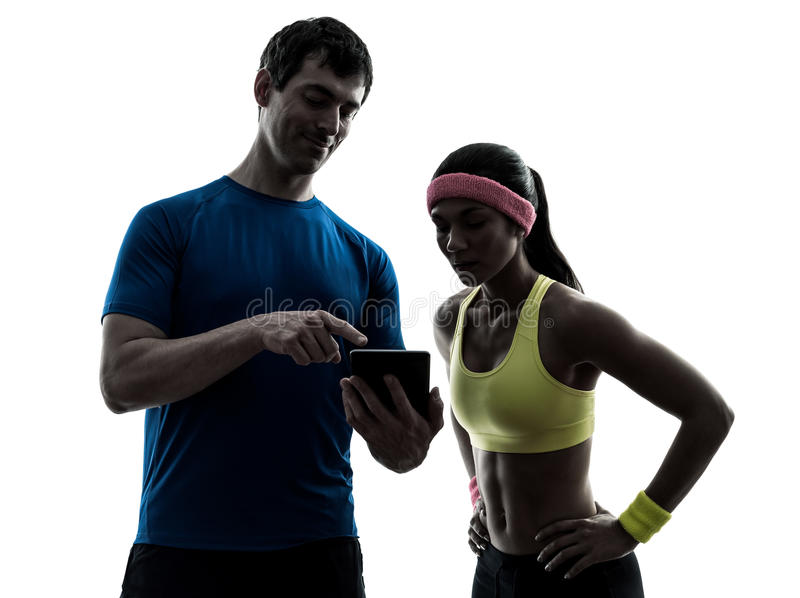 Kobieta ćwiczy sprawność fizyczna mężczyzna pastylki powozowego używa cyfrowego silhou fotografia stock