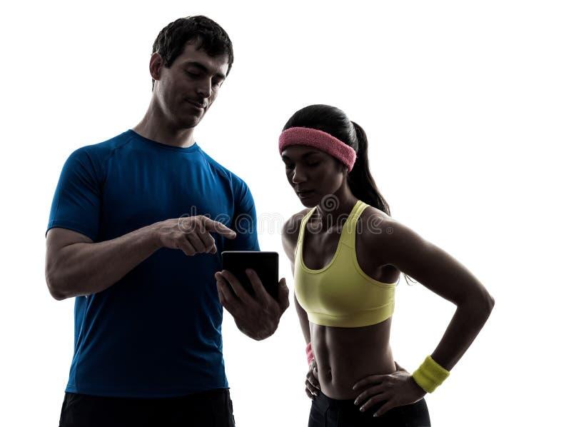 Kobieta ćwiczy sprawność fizyczna mężczyzna powozową używa cyfrową pastylkę fotografia royalty free