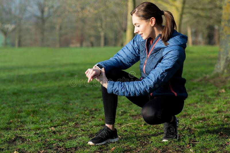 Kobieta Ćwiczy W zima parku Patrzeje aktywność tropiciela Na smart watch zdjęcie stock