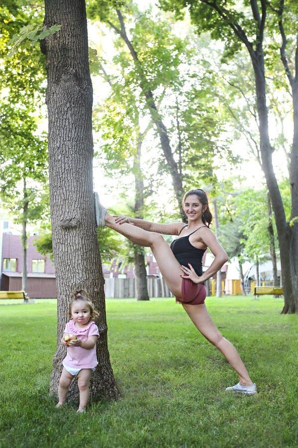 Kobieta ćwiczy z jej dziewczynką w parku obrazy royalty free