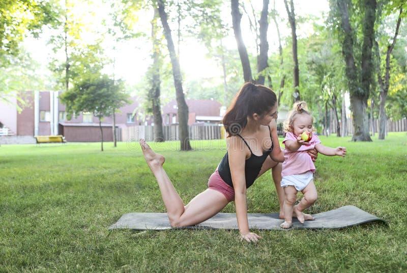 Kobieta ćwiczy z jej dziewczynką w parku fotografia stock