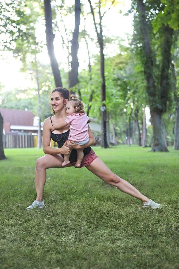 Kobieta ćwiczy z jej dziewczynką w parku zdjęcie royalty free