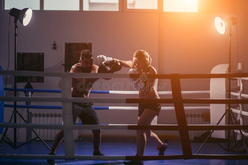 Kobieta ćwiczy z trenerem przy boxe i samoobrony lekcją kosmos kopii zdjęcie stock