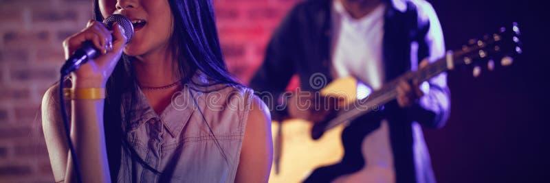 Kobieta śpiew gitarzystą przy klubem obraz stock