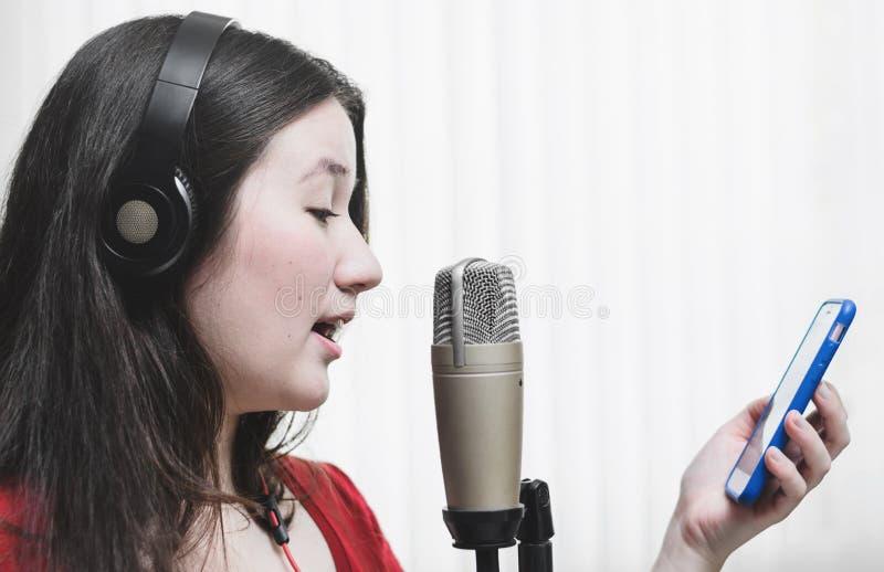 Kobieta śpiew przy pracownianym mikrofonem, jest ubranym hełmofon i ponowny obraz stock