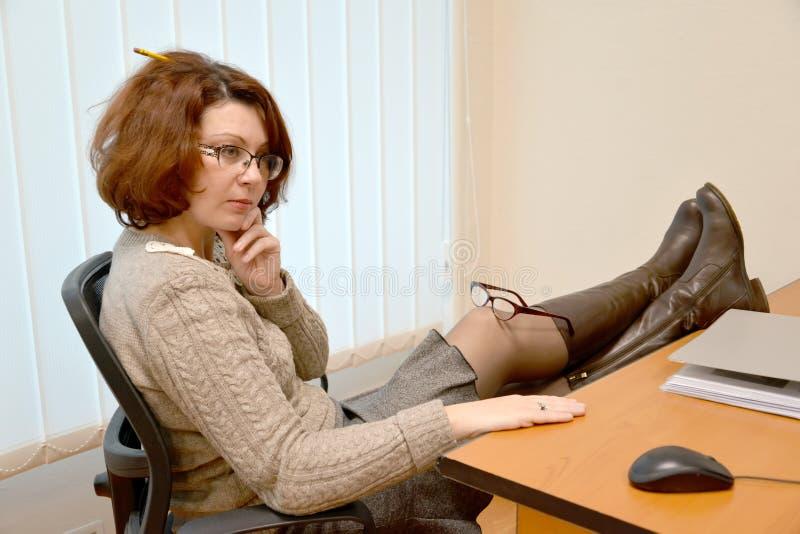 Kobieta średni rok siedzi przy biurem z nogami na stole i szkłach na kolanie zdjęcia stock