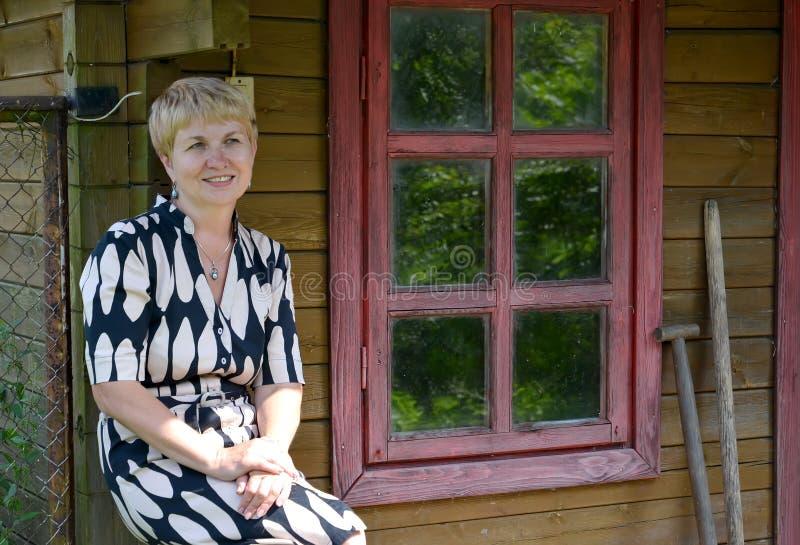Kobieta średni rok zostaje w domu o wiejskim zdjęcie royalty free